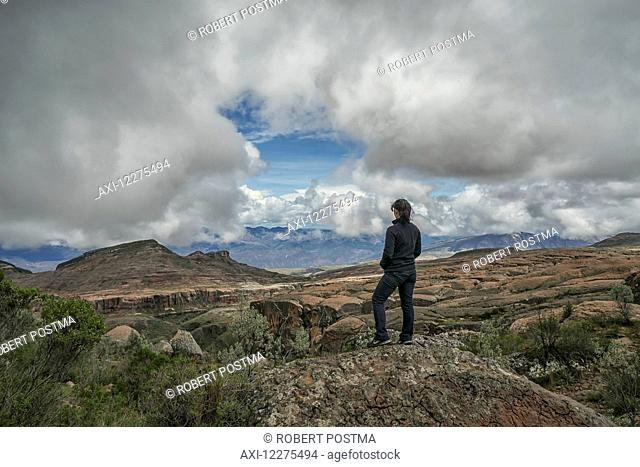 A woman stands on a rock looking out over the beautiful landscape of Toro Toro National Park; Bolivia