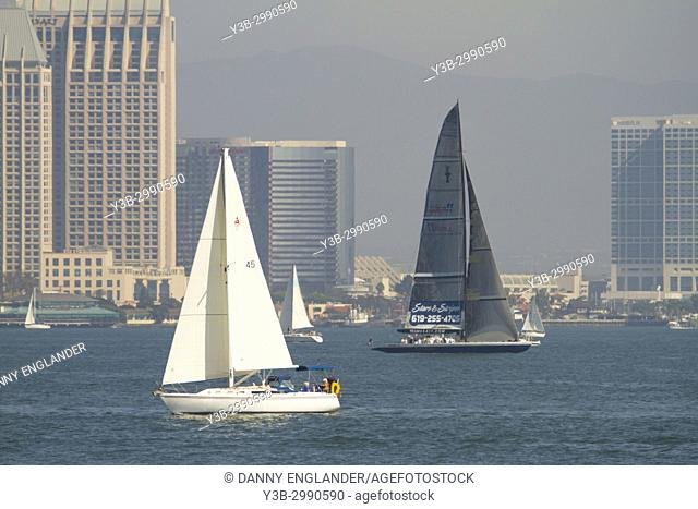 Two sailboats in San Diego Bay, with the city and mountains in the background