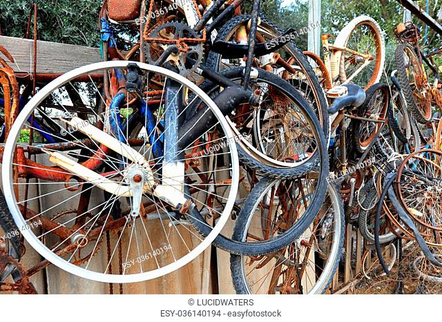 Old rusting bicycles and wheels in a junk yard