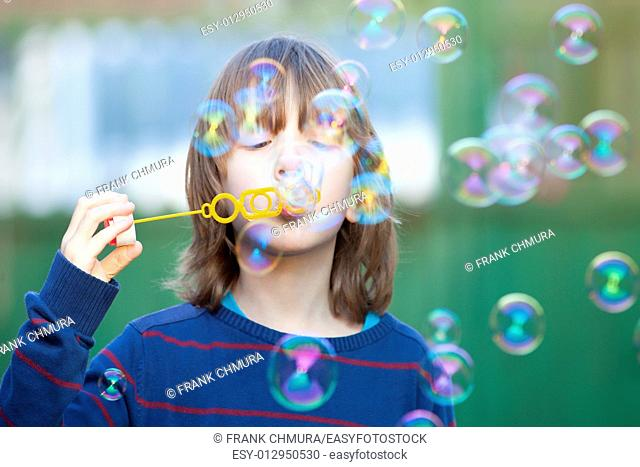 Boy with Blond Hair Blowing Bubbles Outdoor