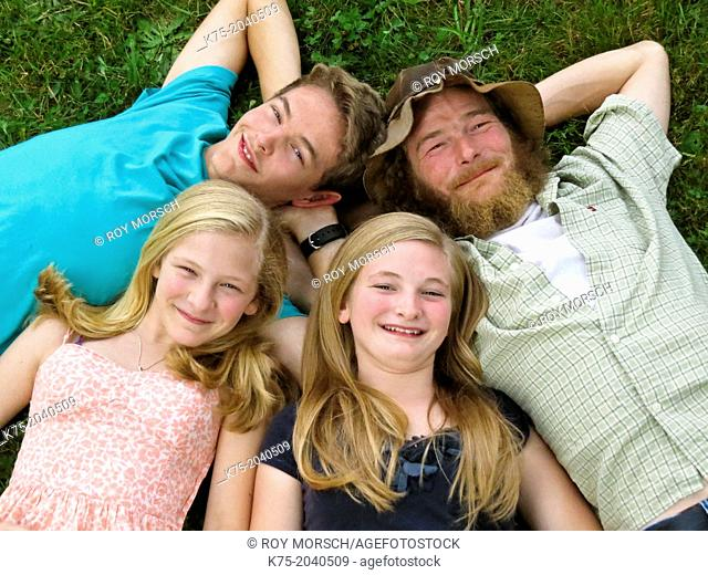 Portrait of family lying down on lawn looking up