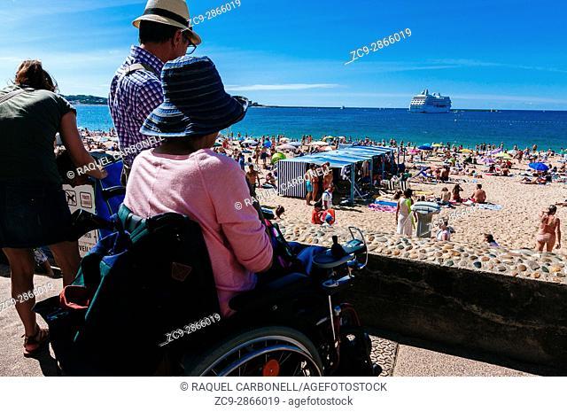 Woman on wheelchair looking over the beach. Saint-Jean-de-Luz, Basque Country, France