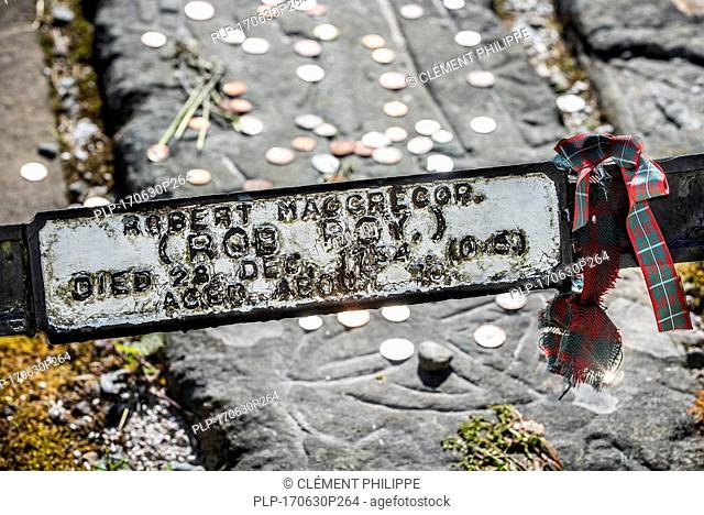 Coins on the grave of Rob Roy MacGregor at the Balquhidder kirkyard, Stirling, Scotland, UK