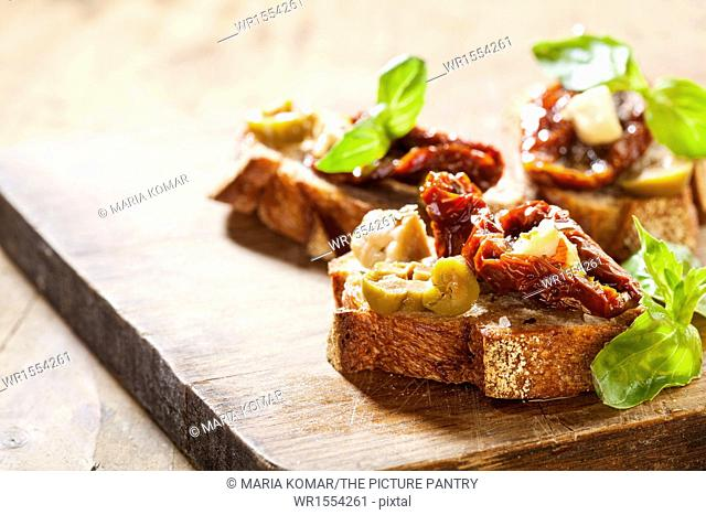 Italian appetizer bruschetta with olive oil, olives, sun-dried tomatoes and cheese