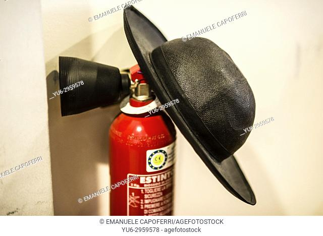 Hat ( Saturno) of a Catholic priest leaning over to a fire extinguisher