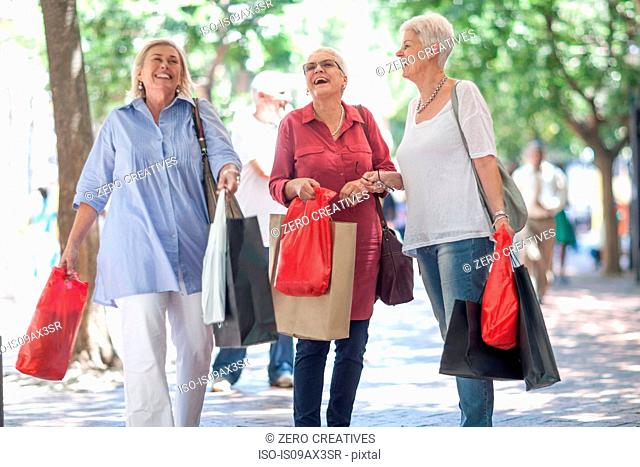 Senior and mature women strolling with shopping bags in city