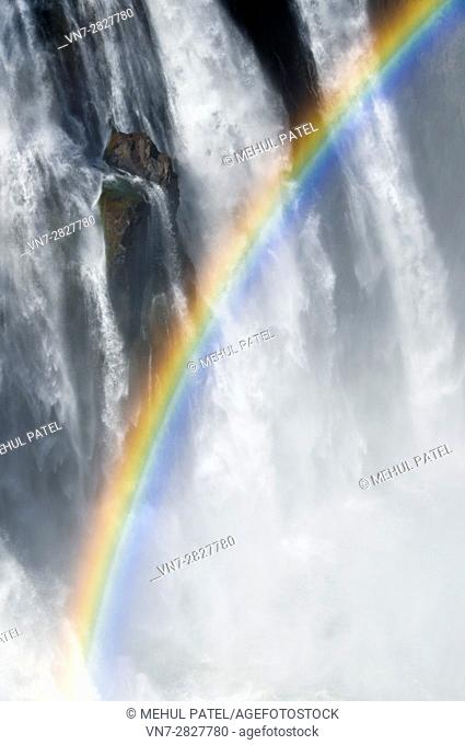 Rainbow amongst the mist, spray and cascading water of Victoria Falls, Africa