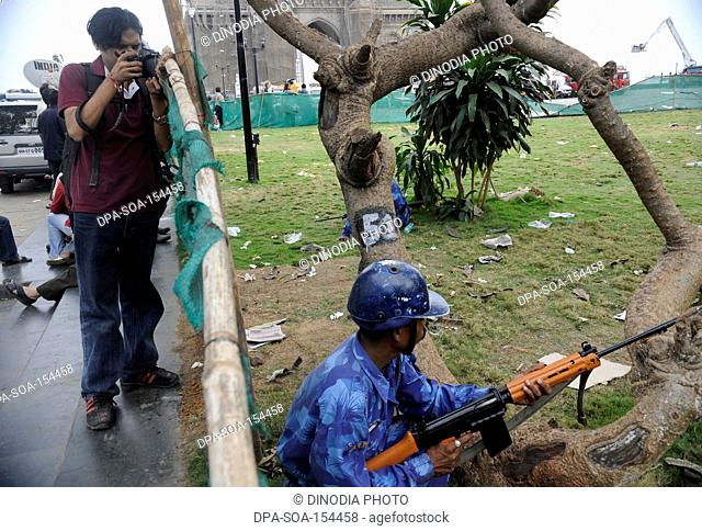 Photographer and Rapid Action Force RAF Commando in a position outside the Gateway of India ; after terrorist attack by Deccan Mujahideen on 26th November 2008...