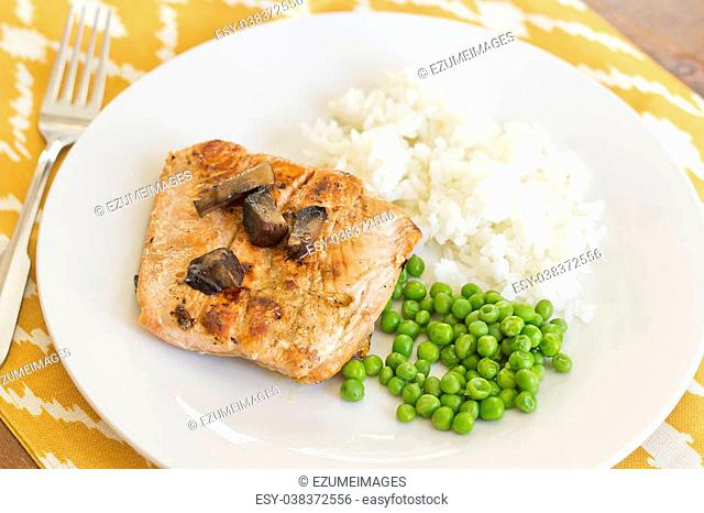 Crispy grilled salmon fillet with roasted portobello mushrooms and sweet glaze with peas and rice on the side