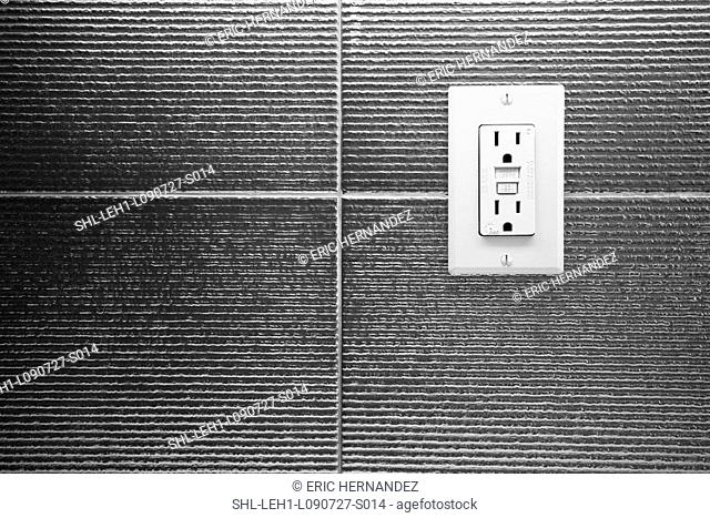 Electrical outlet on tile wall