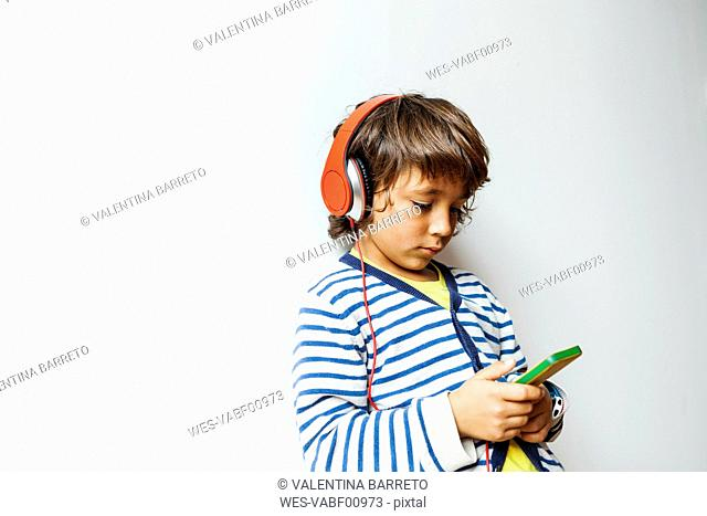 Little boy listening to the music of his smartphone with headphones