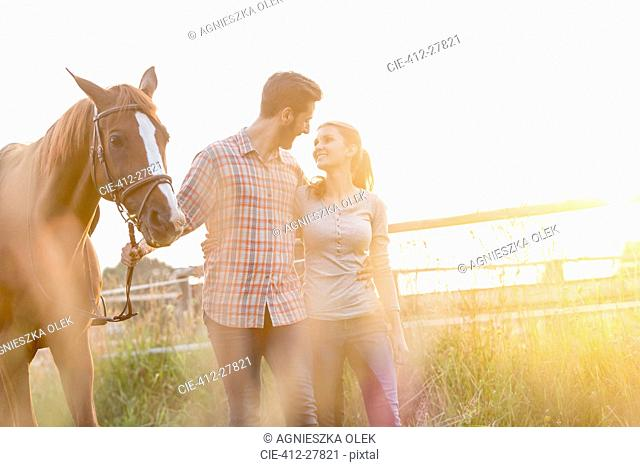 Affectionate couple walking with horse in rural pasture
