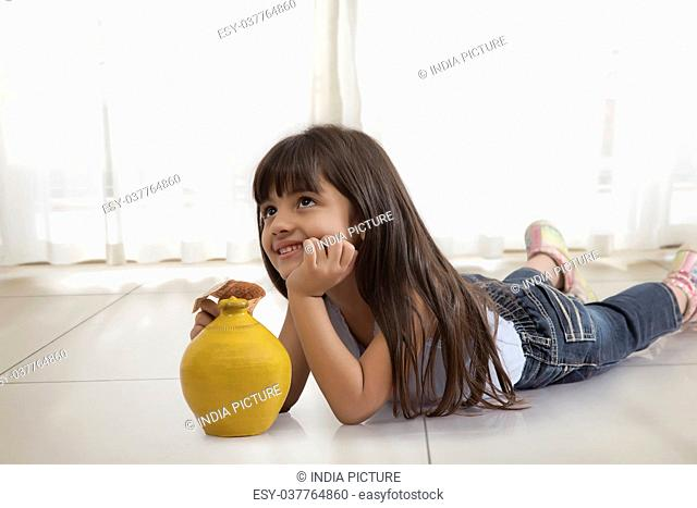 Little girl thinking lying on floor with piggy bank