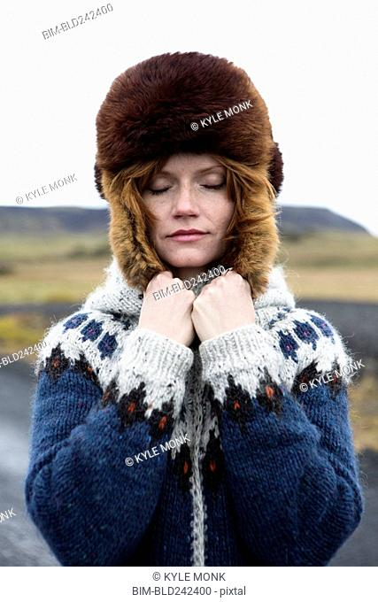 Caucasian woman wearing sweater and fur hat