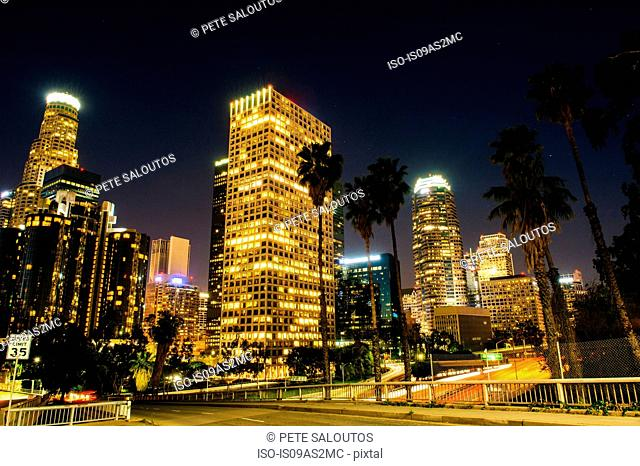 View of highway and city skyline at night, Los Angeles, California, USA