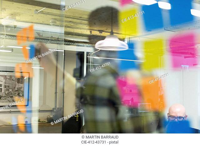 Creative business people brainstorming behind adhesive notes on office window