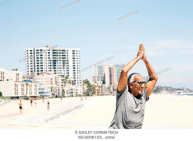 Senior man, exercising on beach, in yoga position, Long Beach, California, USA