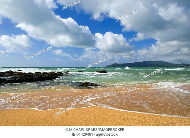 Waves on the orange-red beach of Cable Bay, Doubtless Bay, Northland, North Island, New Zealand