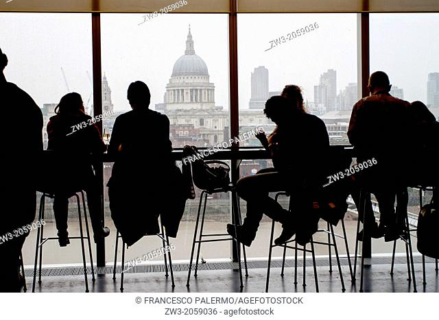 People in silhouette, looking out of large windows. London, United Kingdom