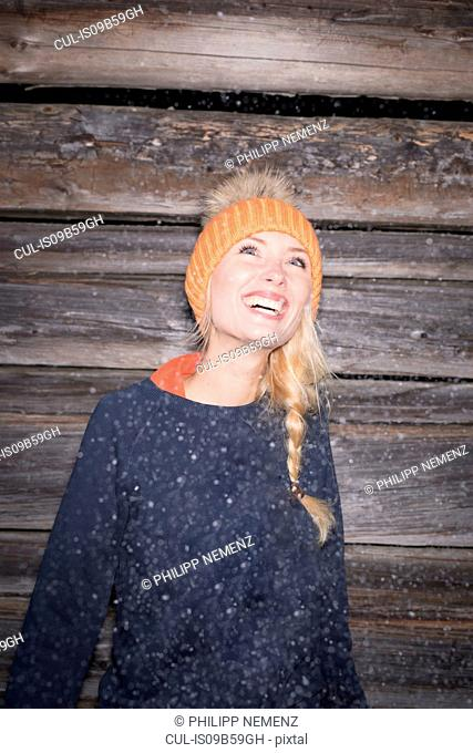Portrait of young woman in orange knit hat looking up