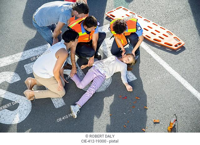 Paramedics examining injured girl on street