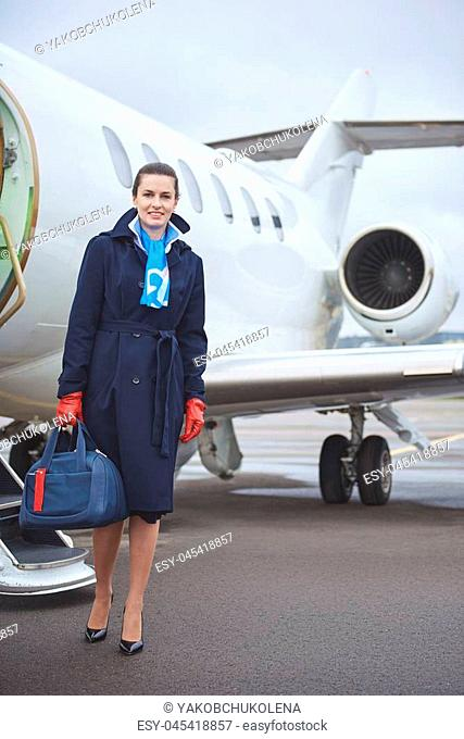 Full length portrait of beaming stewardess holding bag while standing near aircraft outdoor. Job concept