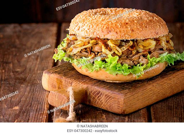 Bagel with stew beef, fresh salad and fried onion on small wooden chopping board over wooden background