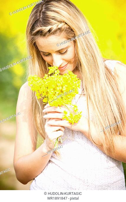 Young woman smelling colza flowers, Tuscany, Italy