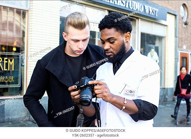 Rotterdam, Netherlands. Barber, working at Schorem Barbers and Haircutters, using a dslar camera to portray his client with new, fresh hairdue