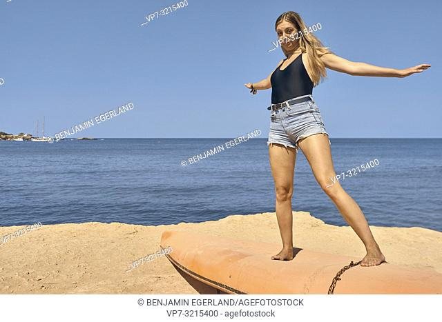 young woman standing on boat at seaside enjoying sunny weather and summer holiday in Crete, Greece