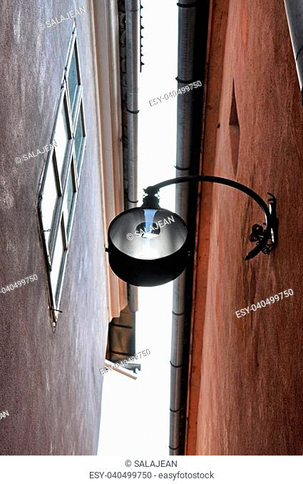 Street lamp hanging in a narrow street