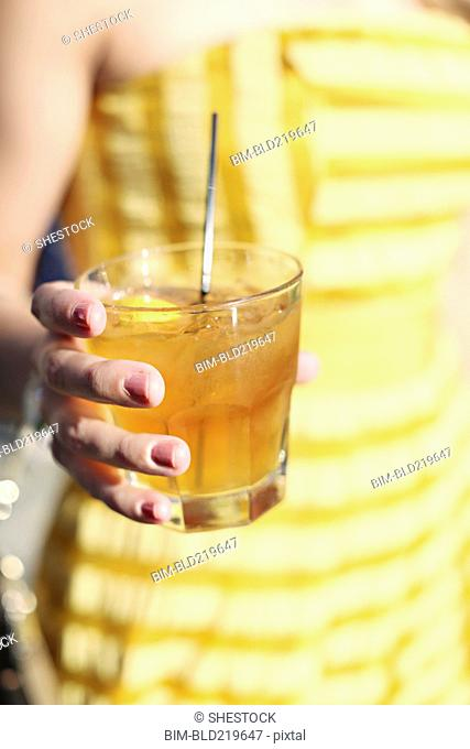 Close up of woman holding yellow cocktail drink
