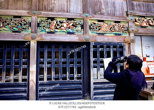 Tourist taking a photograph of Statues of the three wise monkeys embodying the proverbial principle to 'see no evil. Hear no evil. Speak no evil'