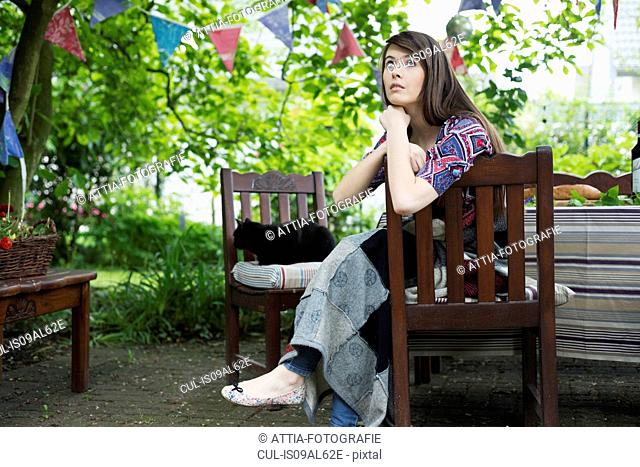 Pensive young woman sitting in garden