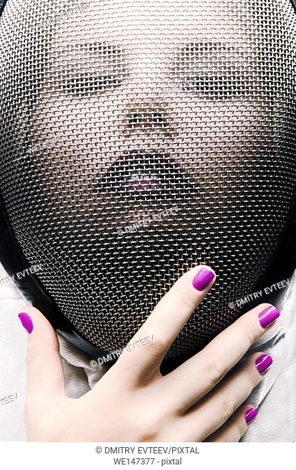Closeup portrait of woman face covered with fencing mask