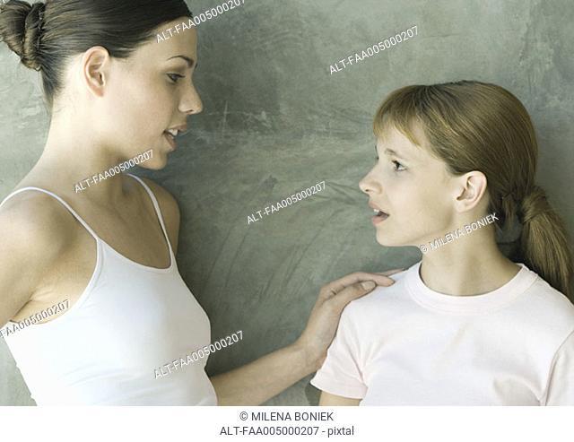 Preteen girl talking to older sister