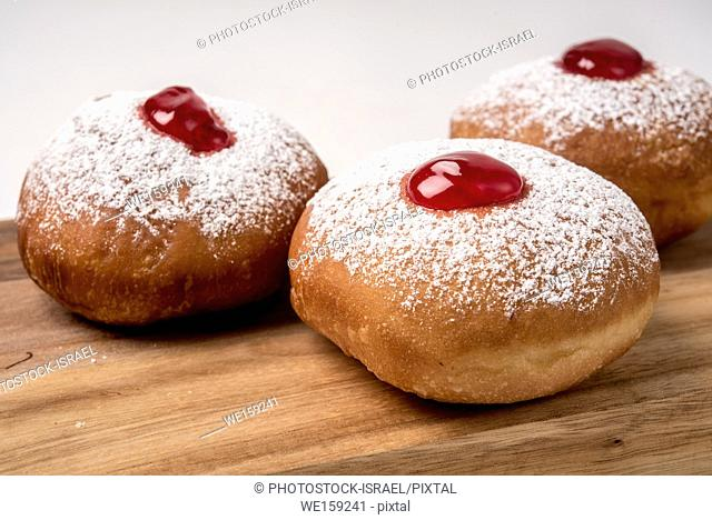 Sufganiyah (sufganiyot) a traditional Jewish Doughnut eaten during Hanukkah with red jam and sugar powder. On white Background
