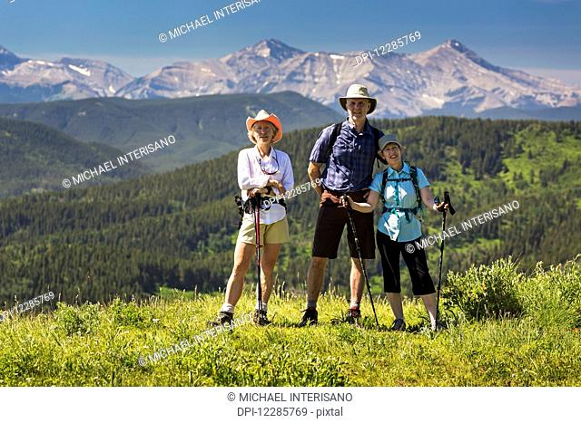 Three hikers, two female and one male, on top of grassy hill with rolling foothills and mountain range in the background with blue sky; Kananaskis Country