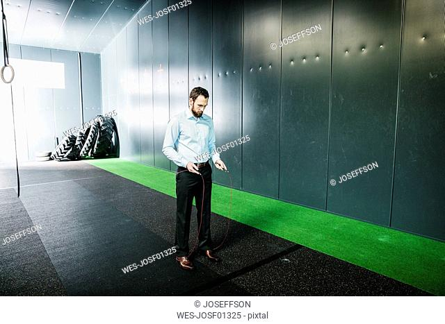 Businessman in gym looking at skipping rope