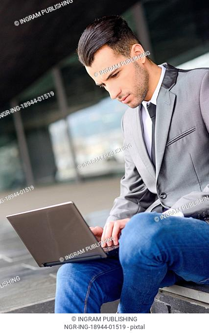 Portrait of attractive young businessman typing in a laptop computer in office building