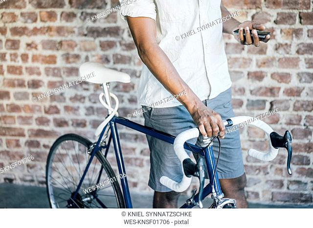 Close-up of man with bicycle checking cell phone
