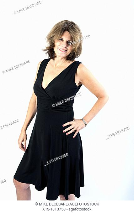 A stylish american woman wearing a black dress poses with her left hand on hip