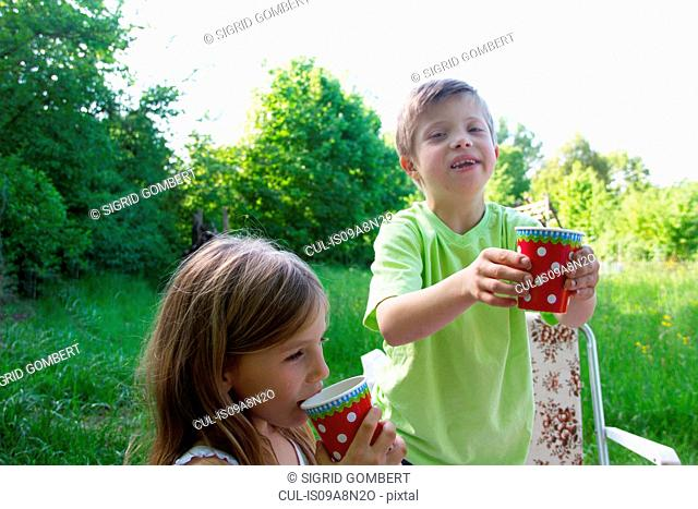 Brother and sister with picnic cups