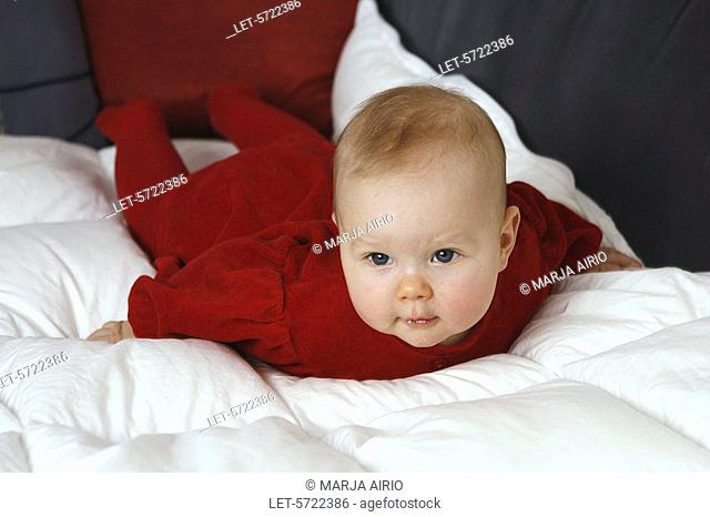 A 6-month-old baby girl dressed in a red playsuit lying on her stomach