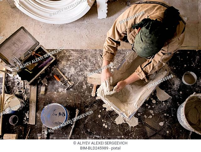 Caucasian artist spreading plaster into mold with hands