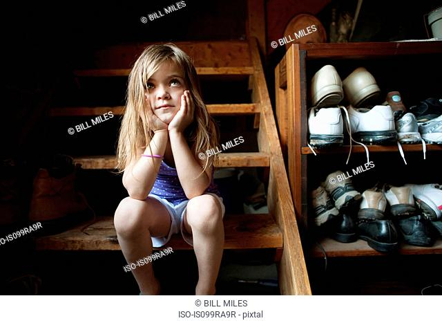 Little girl sitting on basement steps, looking up