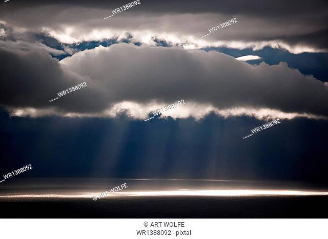 Sun rays stream down thru clouds, Kamai National Park, Alaska, USA