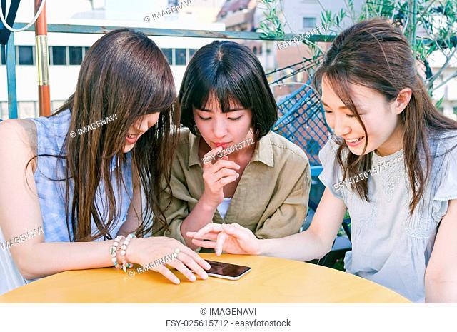 Three women talking and seeing smart phone
