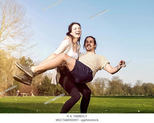Young woman trying to carry her boyfriend