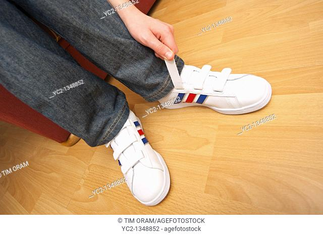 A picture of an eleven year old boy fastening his velcro trainers in the Uk